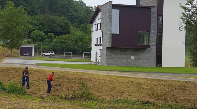 En una imagen de archivo, dos operarios retiran césped recién cortado de parcelas que rodean a la sede del Ayuntamiento del valle de Larraun, enclavada en Mugiro.
