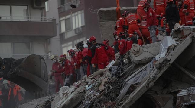 Foto de los miembros del personal de búsqueda y rescate trabajando sobre los escombros en Izmir, Turquía.