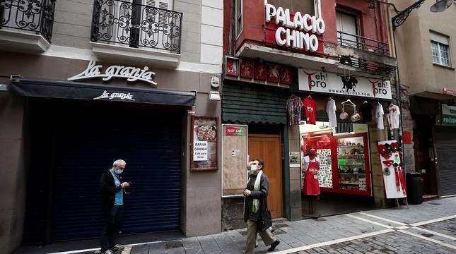 Una tienda de souvenirs situada en la Calle Estafeta permanece abierta mientras que el bar de al lado ha cerrado sus puertas.