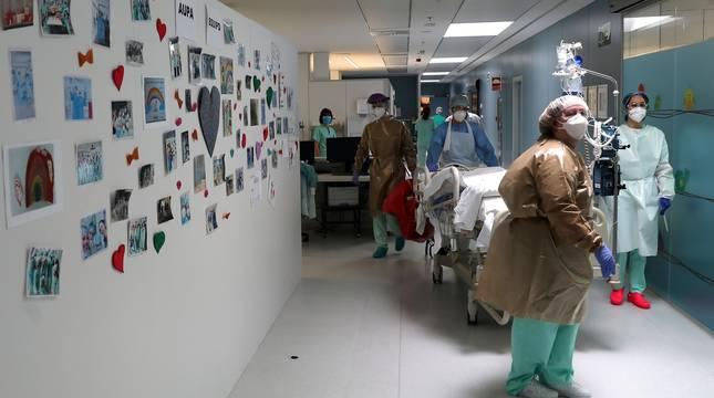 Un enfermo de Covid-19 es conducido a la UCI B, en Pediatría. La pared del pasillo es un compendio de dibujos y mensajes de apoyo que reciben los sanitarios.