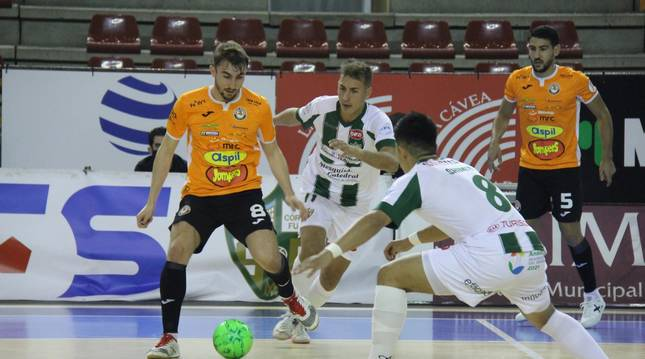 Foto del jugador del Aspil, Javivi, con el balón, intenta marcharse de dos de los hombres de José Antonio González.