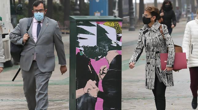 El portavoz Javier Remírez y la presidenta María Chivite pasan junto al destrozado cartel de El beso, camino del Parlamento, una obra del artista callejero LKN, que  pintó a Chivite y Bakartxo Ruiz (Bildu) besándose, por el futuro pacto presupuestario.