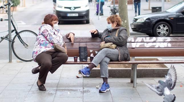 Dos mujeres conversan tomando café en un banco del barrio del Poblenou de Barcelona este jueves.