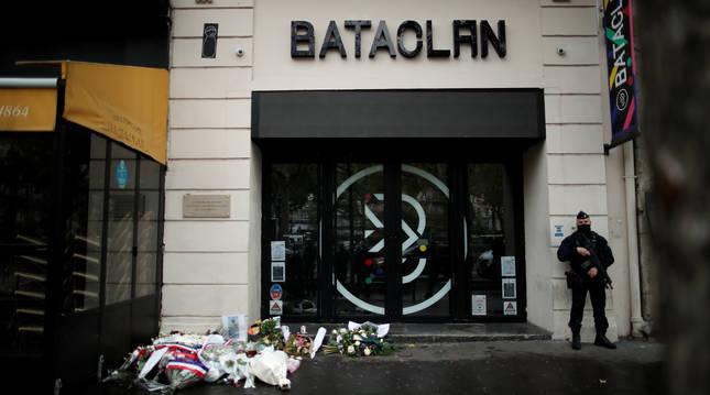 Un policía francés hace guardia a las puertas de la sala Bataclán junto a varios ramos de flores.