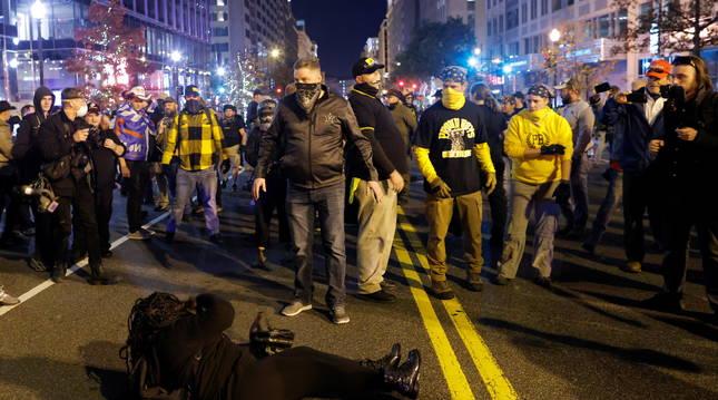 Una mujer yace en el suelo durante una pelea tras una protesta contra los resultados de las elecciones, en Washington.