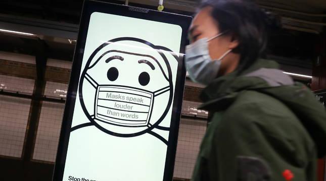 Un pasajero del metro con una mascarilla pasa junto a un anuncio.