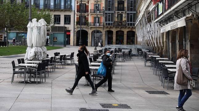 Foto de varias personas pasando junto a terrazas cerradas en la plaza del Castillo.
