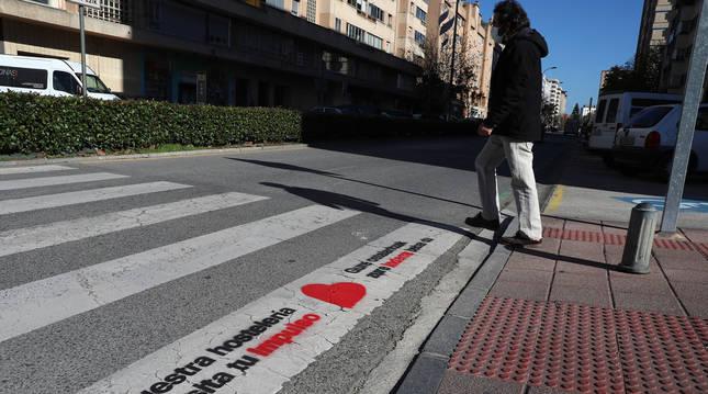 Foto de uno de los pasos de cebra de Barañáin (Navarra) con el eslogan de la campaña de apoyo al comercio local sobrepintado.