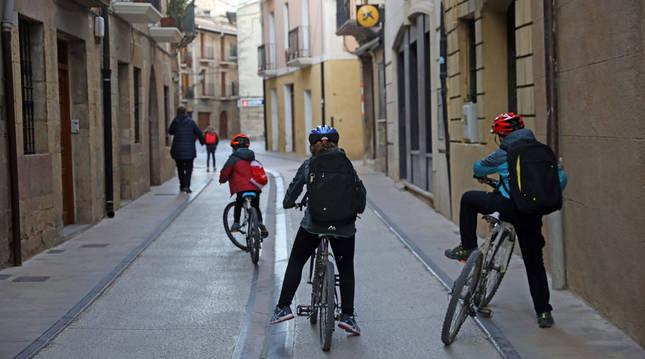 Foto de tres escolares acudiendo al colegio por la calle Mayor empleando la bici.