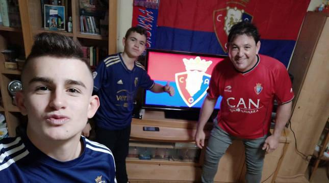 Foto de Aimar Ruiz de Viñaspre, en primer plano, junto a su hermano Iker y su padre Mitxel, con camisetas rojillas en casa.