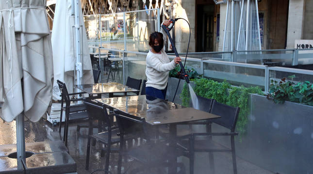 Foto de una trabajadora limpiando las terrazas que se reabrirán a partir de este jueves.