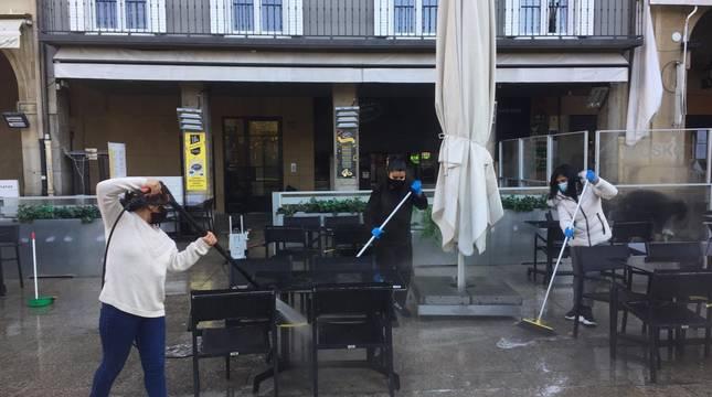 Tres operarias limpian este martes la terraza de 'La Tasca de don José', en la Plaza del Castillo de Pamplona.