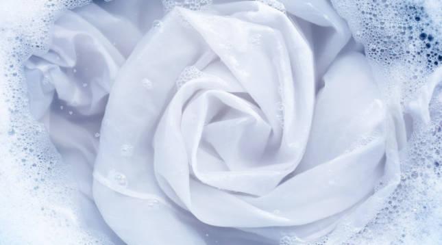 Imagen de ropa blanca sumergida en agua con detergente