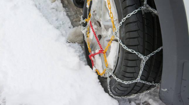 Una rueda de coche con las cadenas para la nieve colocadas