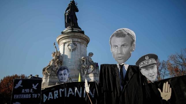 Manifestación en París con la imagen de Macron en una pancarta.