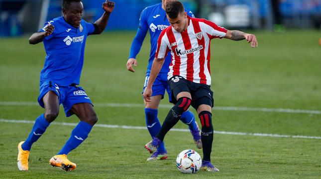 El exrojillo Alex Berenguer controla el balón ante la presión de dos jugadores del Getafe.