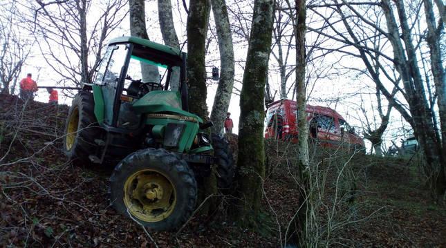 Foto del tractor, que cayó por la pendiente y acabó chocando contra unos árboles.