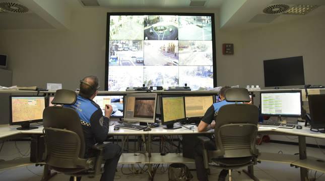 Foto de dos agentes vigilando distintos puntos de Pamplona gracias al sistema de control.