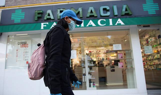 Foto de una viandante, protegida con guantes y mascarilla, pasando por delante de una farmacia del centro de Madrid.