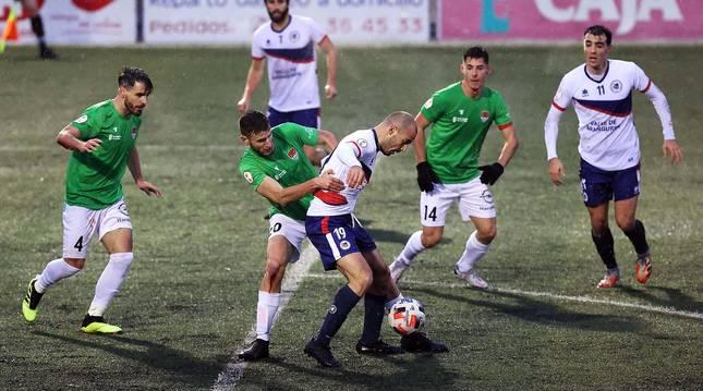 El defensa central del Haro Gaizka Martínez agarra al delantero de la Mutilvera Javi López e intenta robarle la posesión del esférico.