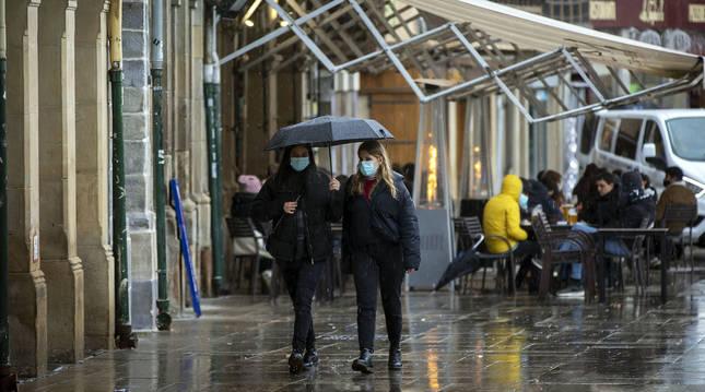 Dos personas cubiertas con mascarilla se protegen de la lluvia con un paraguas en la Plaza del Castillo de Pamplona.