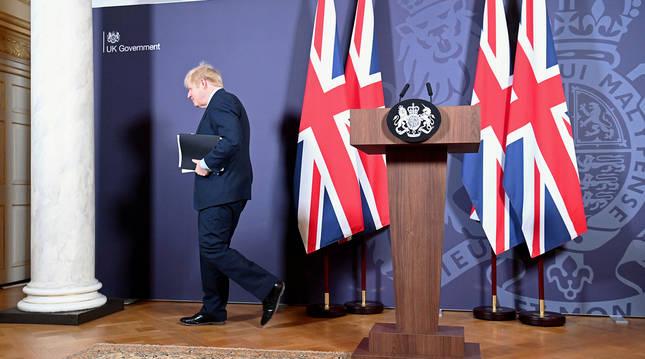 El primer ministro británico, Boris Johnson, sale de la sala tras dar la rueda de prensa posterior al acuerdo en el 10 de Downing Street.