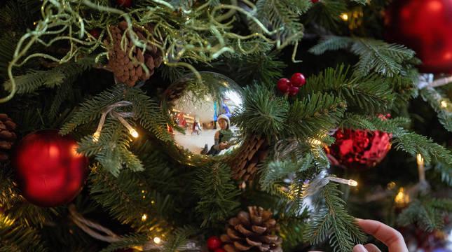 Una mujer, reflejada en la bola de un árbol navideño.