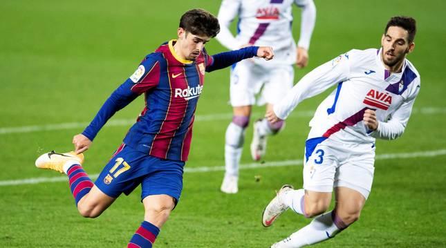 El delantero portugués del FC Barcelona Francisco Trincão (i) centra el balón junto a Pedro Bigas, del Eibar,