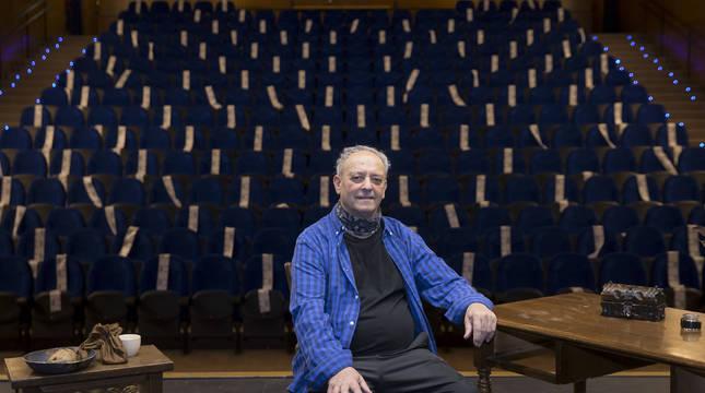 Fernando Eugui sobre el escenario de la casa de cultura de Villava con parte del atrezzo de la obra. Al fondo, la sala de butacas, muchas de ellas precintadas.