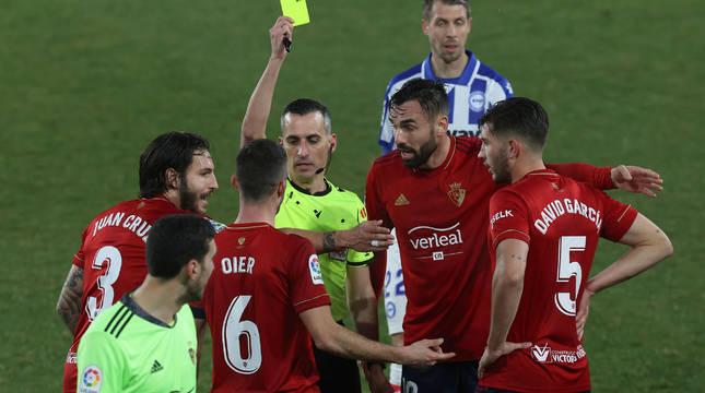 Jaime Latre le muestra tarjeta amarilla a Oier después de la acción con Joselu ante las protestas de los rojillos.