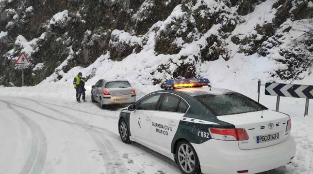 Imagen de un coche de la Guardia Civil auxiliando a otro vehículo en Ibañeta.