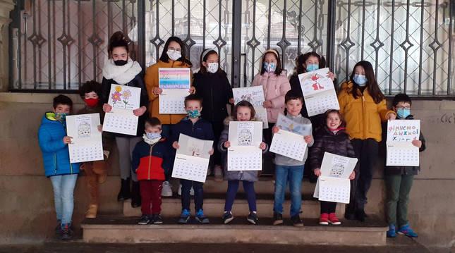Foto de escolares del colegio Luis Gil posan con calendarios que recogen sus dibujos para la residencia.