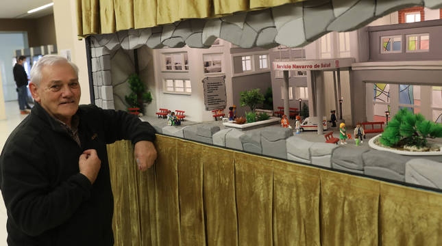 Mateo Viguria posa junto al belén que recrea el edificio principal del Complejo Hospitalario.