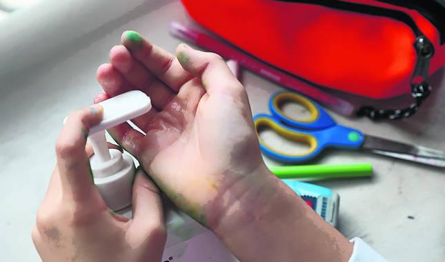 Un niño vierte gel hidroalchólico en la palma de su mano, después de hacer manualidades.