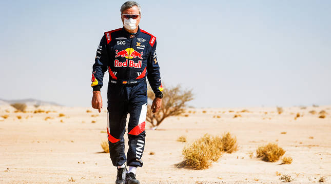 Carlos Sainz camina sobre el desierto durante una pausa en una etapa de Dakar 2021.