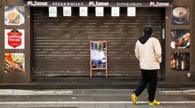 Un hombre observa el cartel de cierre temporal de un establecimiento hostelero en el distrito de Kabukicho, en Tokyo.