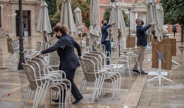 Foto de varios trabajadores de un restaurante del centro de Valencia recogiendo la terraza.