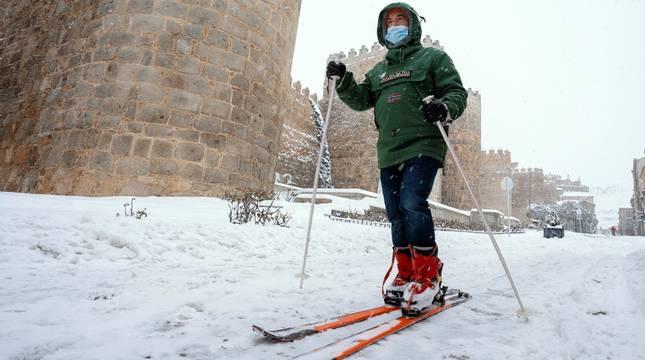 Un hombre esquía junto a la muralla de Ávila este sábado.
