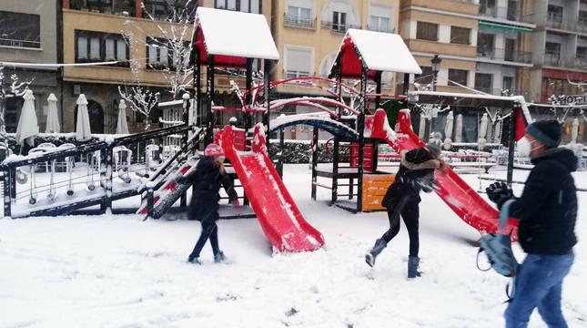 Varias personas disfrutan de la nieve este sábado en el Paseo de Invierno de Tudela.