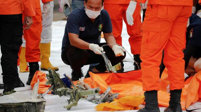 Un técnico analiza restos del avión en el puerto de Tanjung en Yakarta.