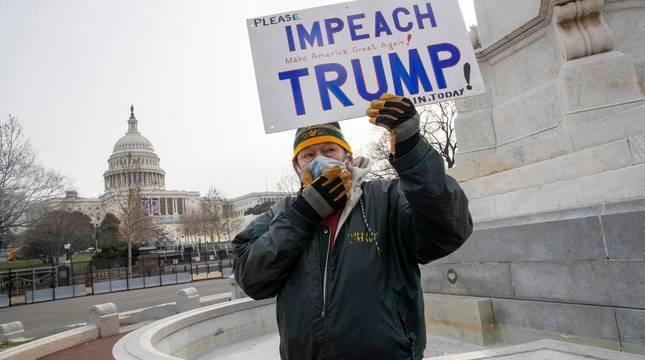 Un hombre, en las cercanías del Capitolio, reclama que Trump sea sometido a un juicio político.