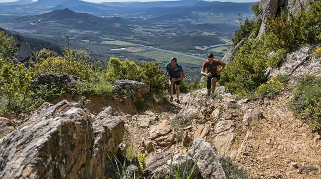 Dos corredores ascienden por la ladera de montejurra por una de las sendas de la montaña