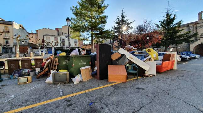 Televisiones, sofás y mobiliario diverso depositado junto a contenedores de la Plaza de los Fueros de Sangüesa en un día de recogida de voluminosos.