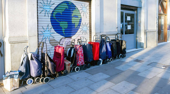 Carros de compra a la espera del reparto de lotes de comida ante la ONG L'Hora de Déu del barrio del Raval de Barcelona