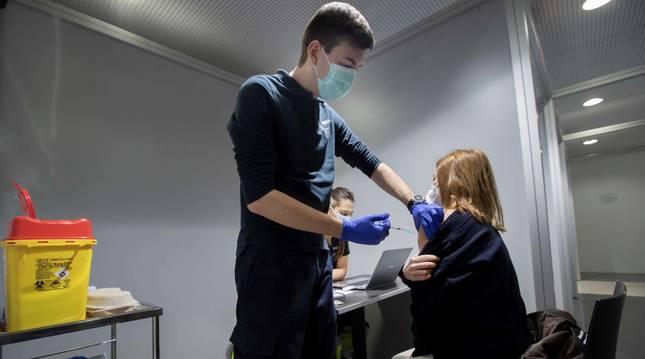 Un enfermero administra la vacuna Pfizer a una sanitaria en las instalaciones de Refena de Pamplona