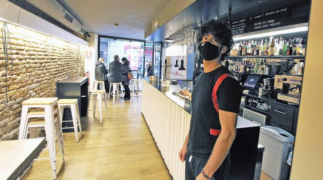 Foto de Adrián Romero, camarero del bar Qwerty, en Mercaderes. Desde el sábado intentarán sobrevivir con cuatro barriles y comida para llevar.
