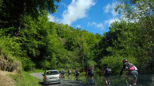 Un vehículo adelanta a un grupo de cicloturistas en la carretera a Beruete (Navarra).