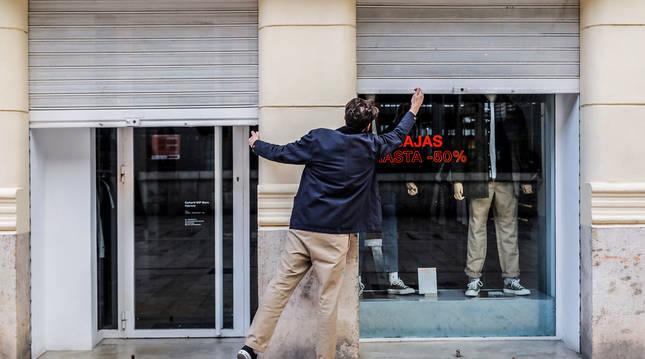 Foto del propietario de un comercio cerrando su establecimiento el primer día del cierre total de la hostelería y de tiendas a las 18.00h en Valencia.