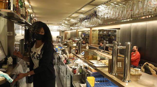 Foto de una trabajadora de El Tinglado, en Pamplona, con clientes en las mesas del local esta semana, antes del cierre de los interiores.