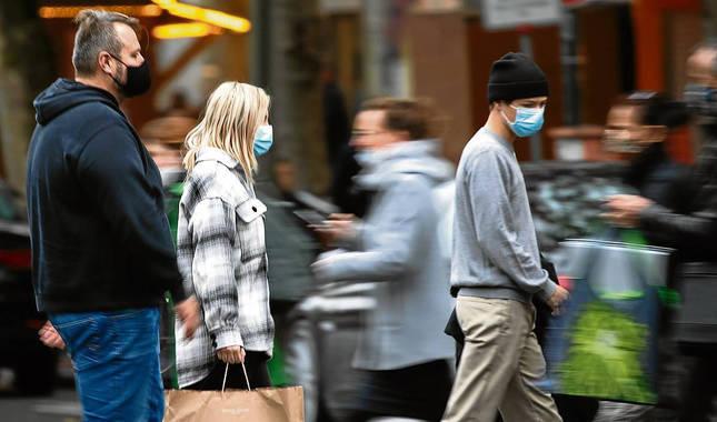 Varias personas pasean protegidos con mascarillas en las calles de Berlín.